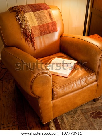 Comfy leather chair with red book and glasses, waiting for a reader - stock photo