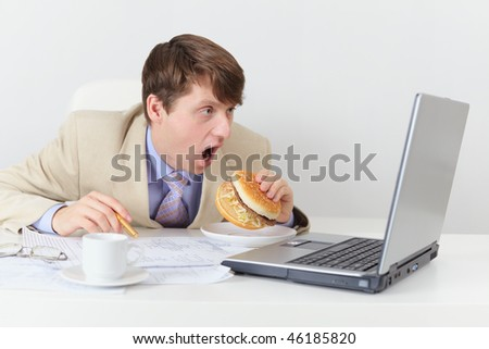 Comic clerk eats a sandwich looking at the screen - stock photo
