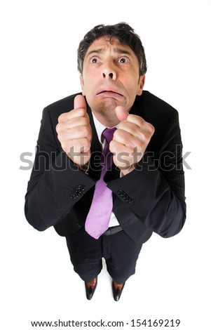Comic high angle portrait of a middle-aged businessman with a scared fearful expression raising his fists to his face as though beseeching help, isolated on white - stock photo