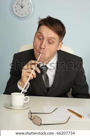 Comic man is drinking coffee with long straws in office - stock photo