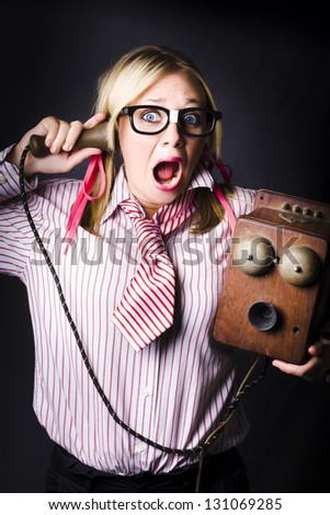 Comic Portrait Of A Nerdy Female Member Of Staff Holding Old Bell Phone With Shocked Expression When Hearing Bad News Announcement - stock photo