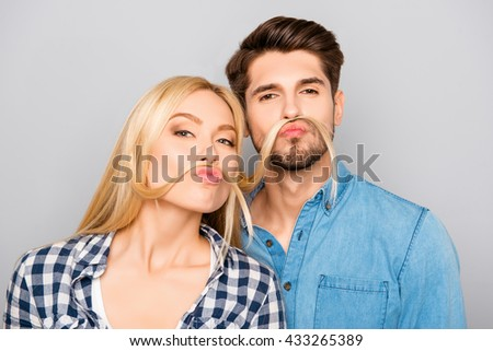 Comic portrait of man and woman making mustache from hair - stock photo