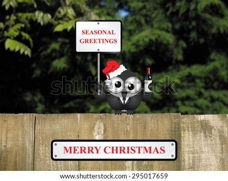 Comical drunk bird with seasonal greetings sign and merry Christmas message perched on a timber garden fence against a foliage background                              - stock photo