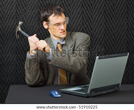 Comical person intends to break computer with hammer