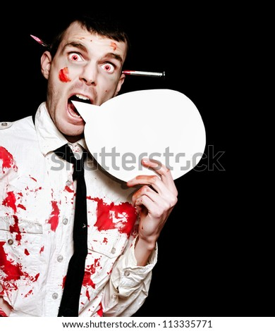 Comical Photo Of A Evil Halloween Zombie Shouting Out A Horror Message Of Blood And Gore Through A Round Speech Bubble On Black Background - stock photo