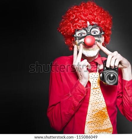 Comical Photograph Of A Smiling Clown Holding Digital Camera In A Cheesy Depiction Of A Happy Snap On Dark Studio Background - stock photo