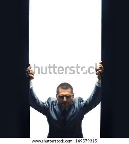 Coming confident businessman by opening some gate - stock photo