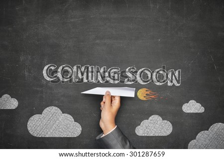 Coming soon concept on black blackboard with businessman hand holding paper plane - stock photo