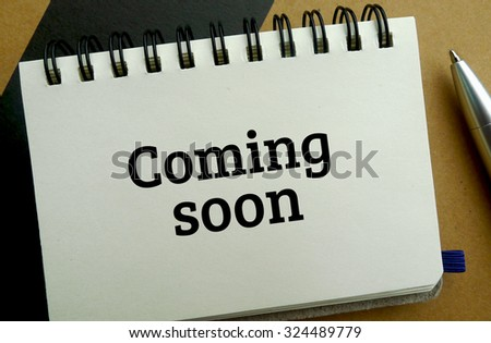 Coming soon memo written on a notebook with pen