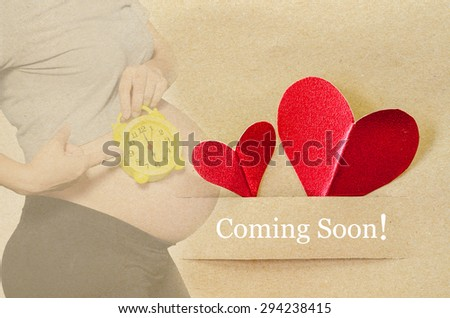 Coming soon. Pregnant woman with red heart on brown paper tag. - stock photo