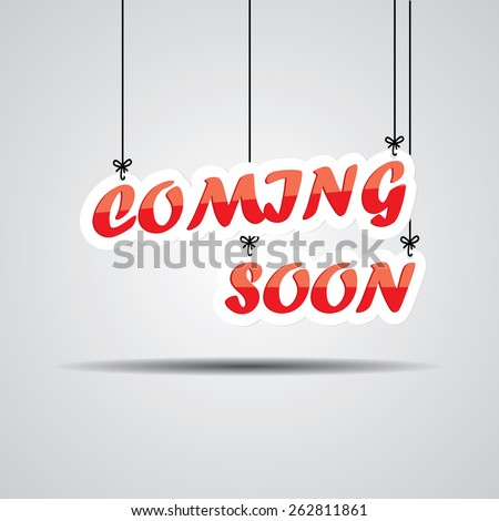 Coming Soon Sign Hanging On Gray Background. - stock photo