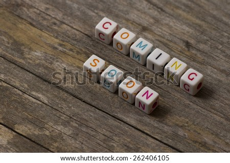 coming soon text on a wooden background - stock photo