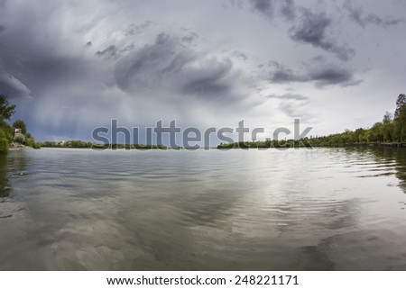 Coming storm over lake - stock photo