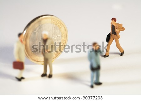 Coming To The Aid Of The Euro, a miniature toy businessman with his briefcase rushes to join his colleagues standing in front of a Euro coin, macro concept. - stock photo