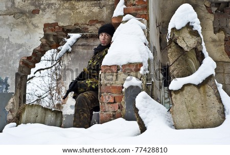 commando.sniper with an weapon on position.warrior is in ruins of city.military action. - stock photo