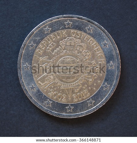 Commemorative 2 Euro coin (Austria 2012 - 10th anniversary of Euro currency circulating) over black background
