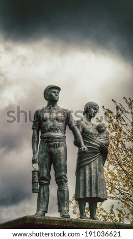 Commemorative vintage  statue of miner, wife and child. - stock photo