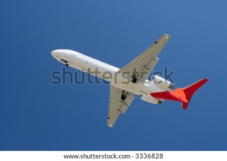 Commercial aircraft against clear blue sky - stock photo