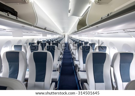 Commercial aircraft cabin with rows of seats down the aisle - stock photo