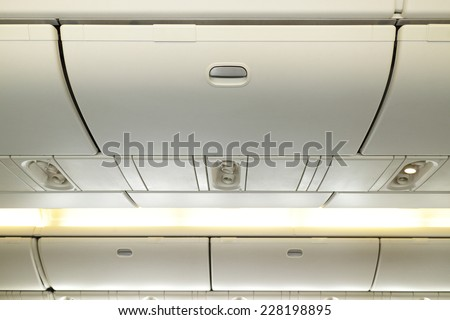 Commercial aircraft interior in airplane cabin, Overhead compartment - stock photo