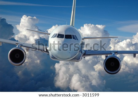 Commercial airliner in flight over a cloud covered background. - stock photo