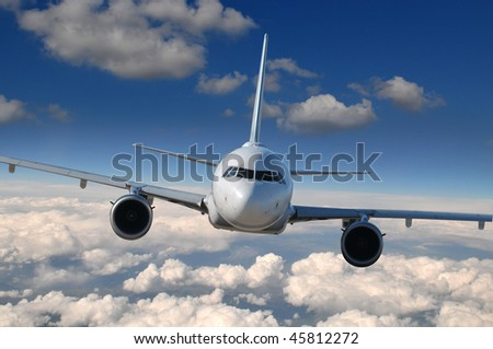 Commercial airliner in flight with clouds on the background - stock photo