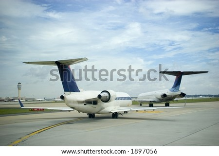 Commercial airliners at a busy airport under a blue sky - stock photo