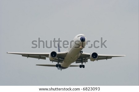 commercial airpalin landing against overcast sky - stock photo