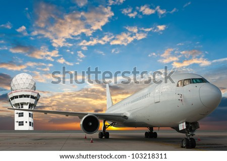 Commercial airplane at the airport with control tower - stock photo