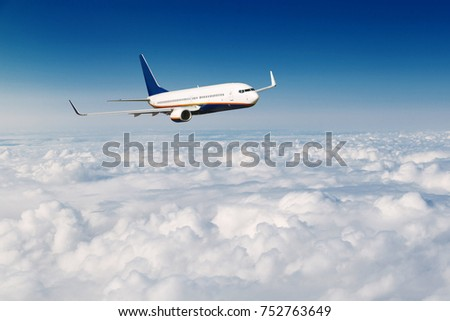 Commercial airplane flying above clouds on blue sky background