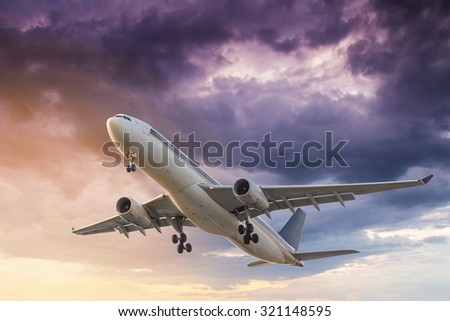 Commercial airplane flying at sunset with storm clouds background - stock photo