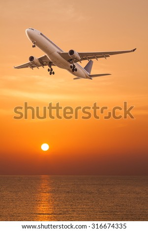Commercial airplane flying over the sea at sunset