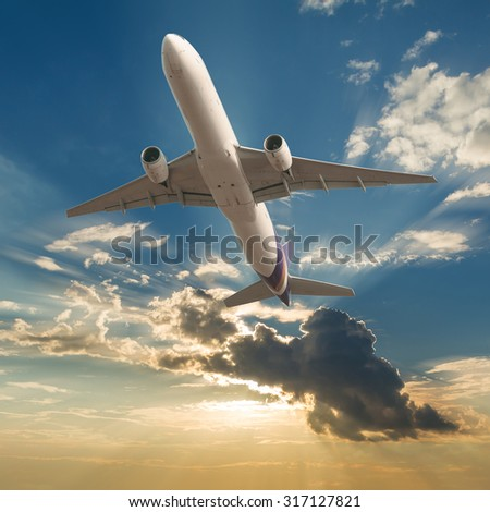 Commercial airplane flying with clouds and sun rays background - stock photo