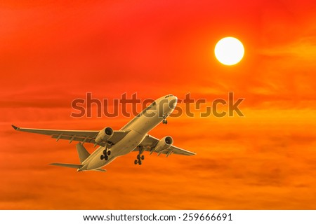 commercial airplane flying with sunset background - stock photo