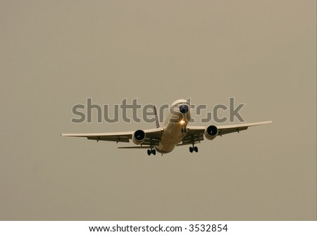 Commercial airplane landing in the evening - stock photo