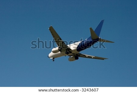 Commercial airplane landing under clear blue sky - stock photo