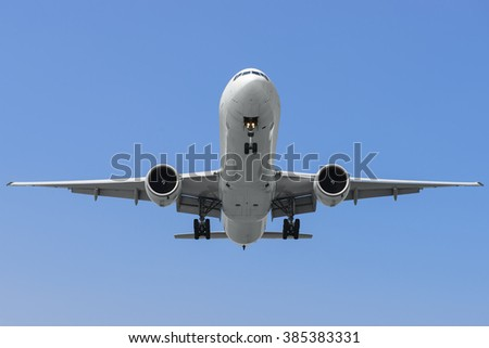 Commercial airplane on finals runway against blue sky