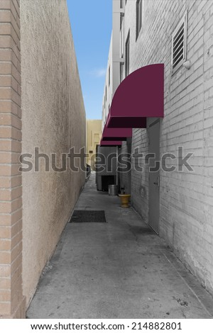 Commercial building paved alleyway with row of purple awnings. Narrow city alley with gray brick and beige stucco texture walls. Window openings. Blue sky background. Vertical composition.  - stock photo