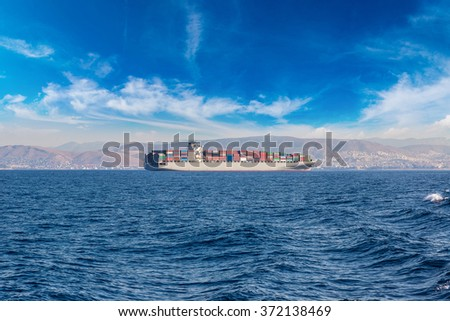 Commercial cargo ship carrying containers in a summer day