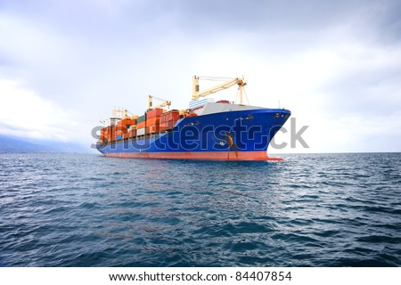 commercial container ship with dramatic sky - stock photo