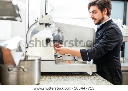 Commercial cook or chef slicing cold meat on a large rotary cutter in restaurant or hotel while preparing ingredients for the evening meal - stock photo