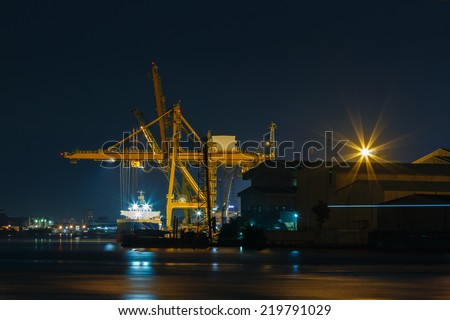 Commercial docks at  night with a ship and cranes - stock photo