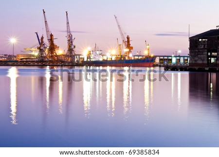 Commercial docks at sunset with a ship and cranes - stock photo