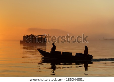 Commercial Fishermen at Sunset. Commercial salmon fishermen, silhouetted against the setting sun, bring their catch to the buyer boat in the background in the Puget Sound area of Washington State. - stock photo