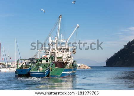 commercial fishing boat leaving harbor at Tirilye (Zeytinbagi) near to Bursa, Turkey  - stock photo