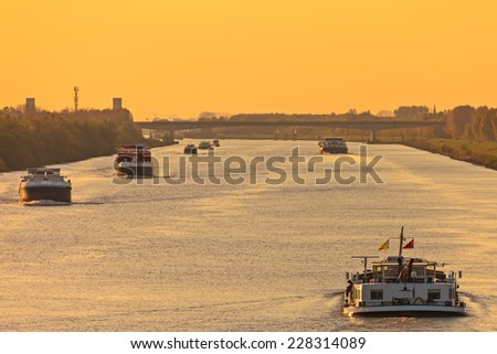 Commercial freight boats on a canal in The Netherlands during sunset - stock photo