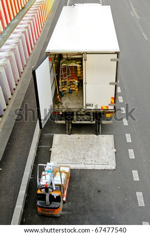Commercial good delivery truck and forklift vehicle - stock photo