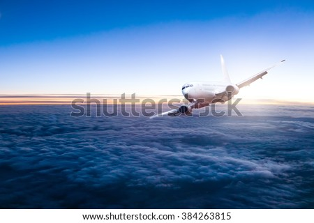 Commercial jet aeroplane flying above clouds - stock photo