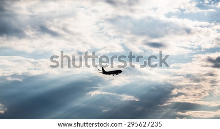 Commercial jet airliner flying toward clouds - stock photo