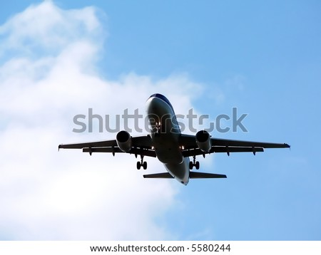 commercial jet in flight with a bright blue sky in the background. copy space included - stock photo